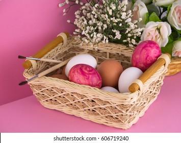 Easter eggs in basket on pink background