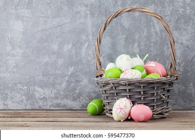 Easter eggs in basket on shelf in front of stone wall. View with copy space