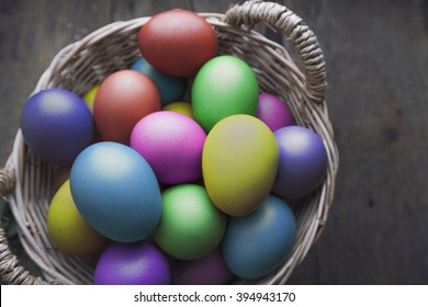 Easter eggs in basket on wooden board