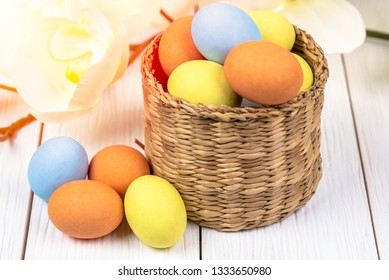 Easter Eggs in a Basket with Orchid Flowers in Background on a Wooden Table. Selective Focus