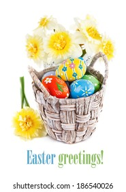 Easter eggs in basket with spring flowers. Isolated on white background