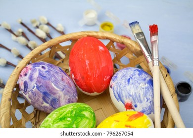Easter eggs in basket. Willow branches. Paints. Easter concept background