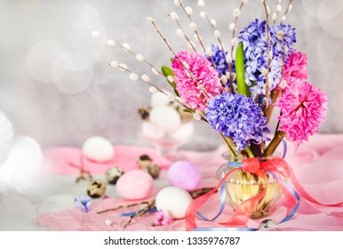 Easter eggs with beautiful hyacinths and willow bouquet on light background, spring holiday concept