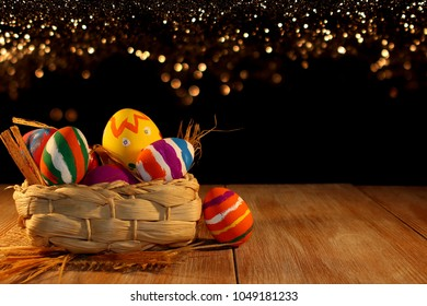 Easter eggs, beautiful multi-colored Easter eggs lie on the straw on wooden boards
