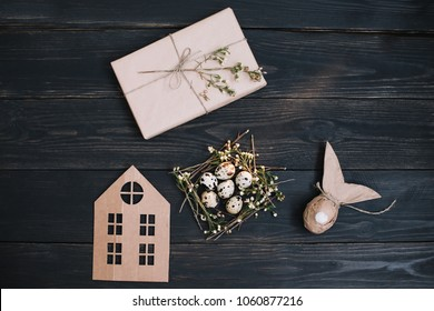 Easter eggs in birds nest on dark wooden background with happy gift tag sign message greeting. Rustic easter still life with quail eggs, dry willow branches on wooden background. Flat lay, top view