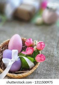 Easter eggs with bowknot and decorative roses in basket on burlap surface. Easter holiday greeting card. Selective focus. Place for text.