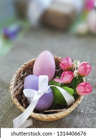 Easter eggs with bowknot and decorative roses in basket on burlap surface. Selective focus. Place for text.