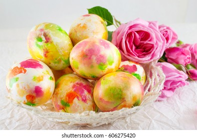 Easter eggs in a bowl and pink roses bouquet