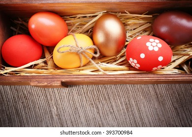 Easter eggs in a box filled with hay, top view