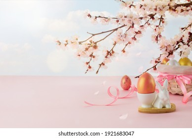 Easter eggs and bunny on pink background. Easter concept. Spring or summer backdrop with branch of cherry tree on blue sky backdrop with copy space.