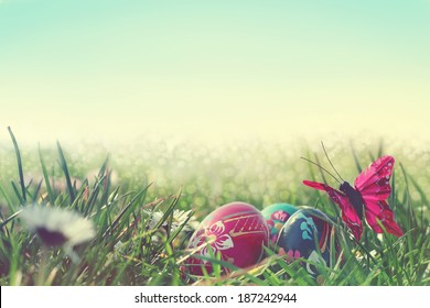 easter eggs with a butterfly and daisies in the grass, vintage photo
