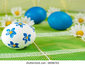 Easter eggs with chamomiles over green background