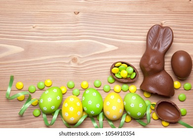 Easter eggs, chocolate easter bunny, candies and ribbon on wooden background.