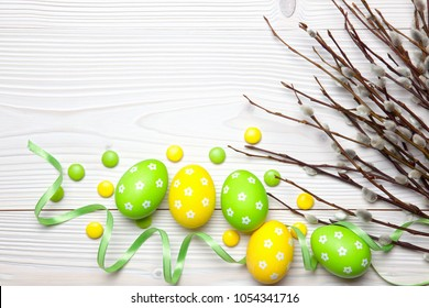Easter eggs, chocolate candies and willow branches on white wooden background.