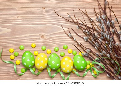 Easter eggs, chocolate candies and willow branches on wooden background.