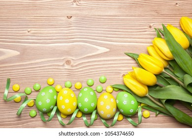 Easter eggs, chocolate candies and yellow tulips on wooden background.