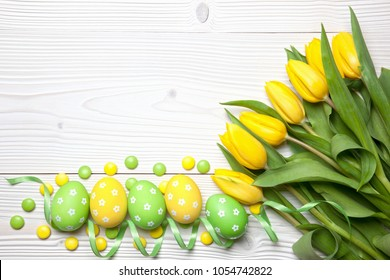 Easter eggs, chocolate candies and yellow tulips on white wooden background.