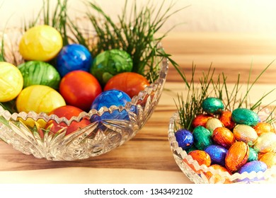 Easter eggs and chocolate eggs on walnut background with bright vignette.