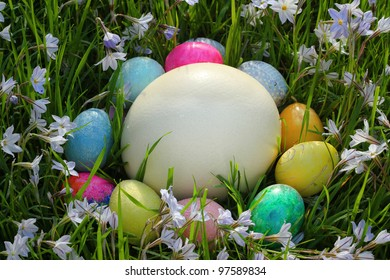 Easter Eggs circled around a large Ostrich egg amid violets.