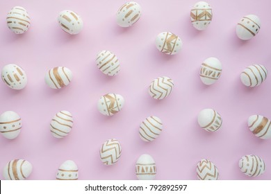 Easter eggs color white and gold on pastel pink background, top view, flat lay, Easter holiday concept.