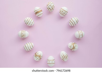 Easter eggs color white and gold on pastel pink background, top view, frame, Easter holiday concept.