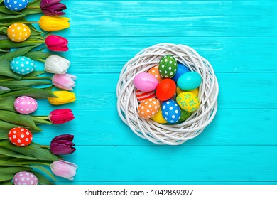 Easter eggs with colorful tulips on wooden background, easter holiday concept.