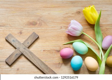 Easter eggs and cross on abstract wooden spring background