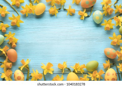 Easter eggs and daffodil flower on wood