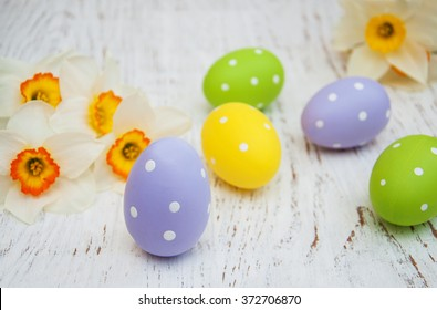 Easter eggs and daffodils flowers on a old wooden background