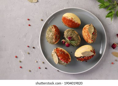 Easter eggs decorated with different spices and cereals without dyes and preservatives on a plate on a gray concrete background. View from above