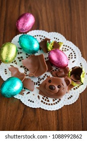 Easter eggs and face of a teddybear made of chocolate on wooden