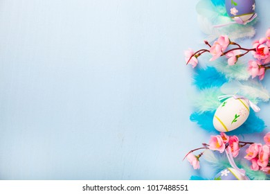 Easter eggs, feathers and flowers on color wooden background. Easter still life with flowers, nest, feathers and eggs.