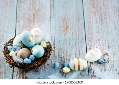 Easter eggs, feathers in a nest on a blue wooden background. The minimal concept. Top view. Card with a copy of the place for the text.