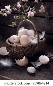 easter eggs and feathers in wicker basket on old wooden background