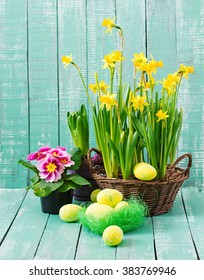 Easter eggs and flowers on a light wooden background