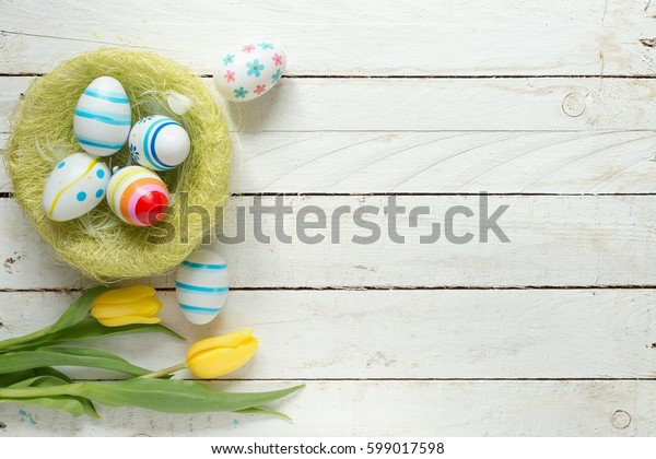Easter eggs and flowers on table/Decorated Easter eggs and flowers on wooden background
