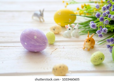 Easter eggs with flowers and rabbits toys on a white wooden table.