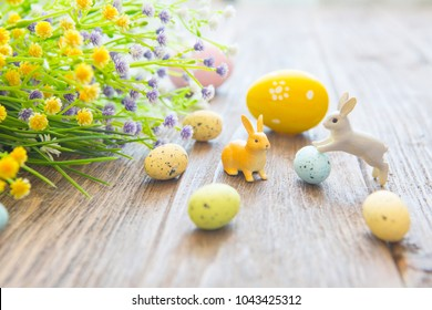 Easter eggs with flowers and small bunny toys on wooden board, easter holiday concept.