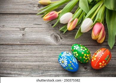 Easter eggs and fresh spring tulips on weathered wooden background