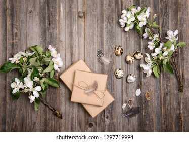 Easter eggs and gift boxes on rustic wooden background. Quail  eggs and spring apple blossom on a old wooden background. Vintage style picture.