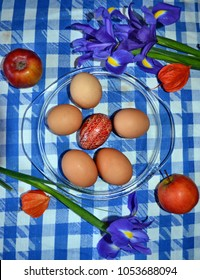 Easter eggs in glass plate, iris flowers, apples and cape gooseberries on the blue-white checked tablecloth, vertical view, Easter background