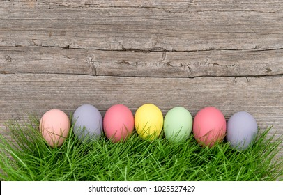 Easter eggs in green grass on rustic wooden background