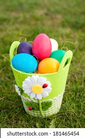 Easter eggs in a green pot on the grass