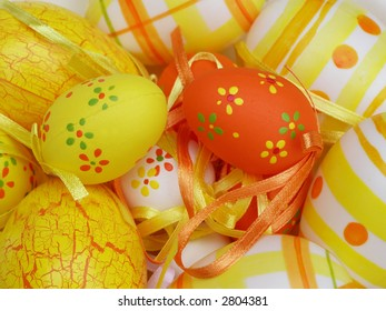 Easter eggs with green, yellow and orange decorations in a group on a table