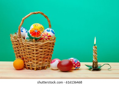 Easter eggs hand-painted near a wicker basket with eggs and candle