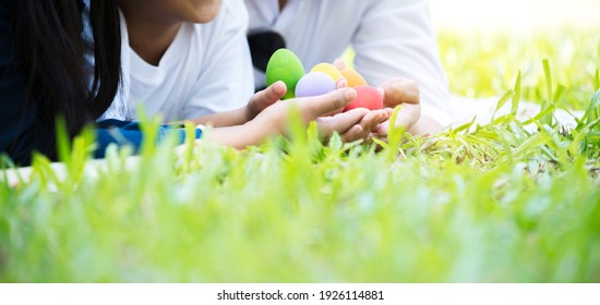 Easter eggs in hands  on green grass floor at the  park, selective focus, copy space.
