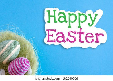 Easter eggs inside basket decorated with woolen threads on blue background with text Happy Easter