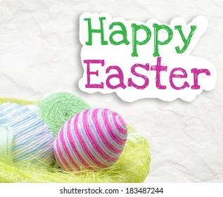 Easter eggs inside basket decorated with woolen threads on paper background with text Happy Easter