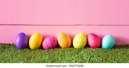 Easter Eggs laying in Green Grass in a row against bright pink wood board background.  Extra wide horizontal crop