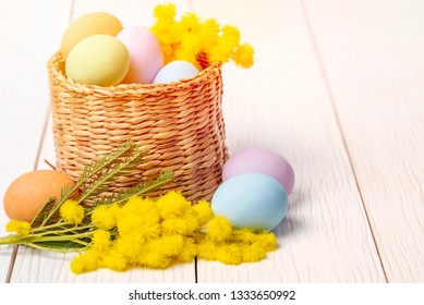Easter Eggs and Mimosa Flowers in Front of and Inside a basket on a Wooden Table. Selective Focus.